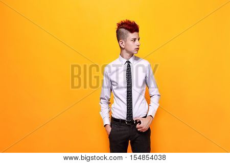 Portrait of displeased teen punk in shirt and tie looking away with hands in pockets.Isolated