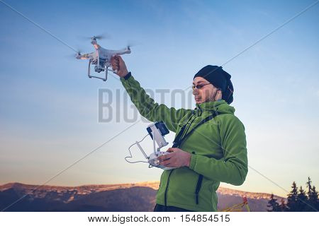 Young man in green jacket holding a drone and remote controller. Ski resort in the background, winter landscape with pine tree forest and mountains. Bukovel, Carpathians, Ukraine, Europe