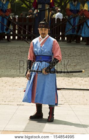 Seoul Korea - May 14 2015: Armed guards in traditional costume guard the entry gate at Deoksugung Palace a tourist landmark in Seoul South Korea