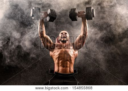 Bald topless man exercising with two dumbbells on bench press in smoke in studio