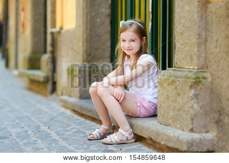 Adorable Little Girl Sitting On A Doorstep