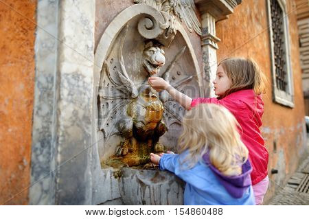 Two Girls Playing With Drinking Water Fountain