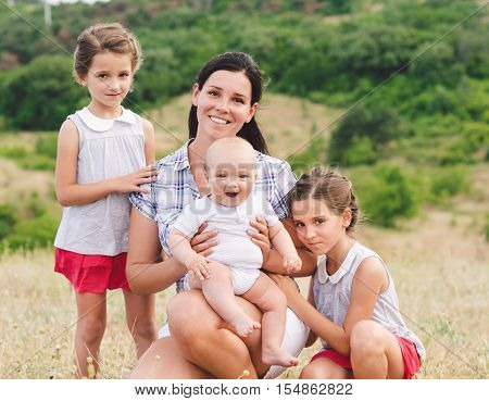 Beautiful young mum and her Children walking in Park together. Happy family.