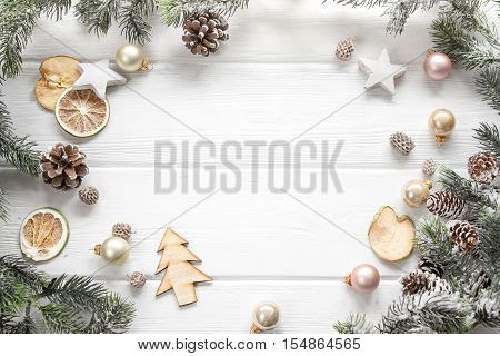 Christmas decoration of fir tree and conifer cone on wood background top view. Copy space