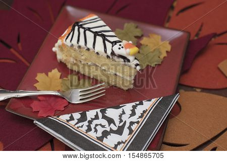 White frosting Hallowen cake with orange and black icing and candy ghosts served on a red plate with fork