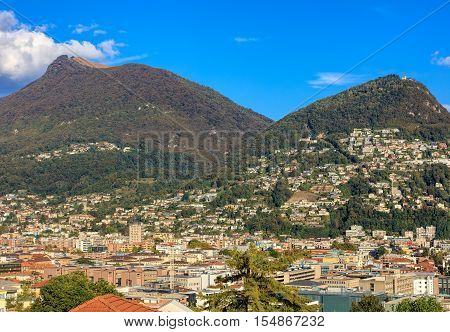 Lugano, Switzerland - 12 October, 2016: view on the city with mountains Monte Boglia and Monte Bre in the background. Lugano is the largest city of the Swiss canton of Ticino.