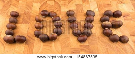 Autumn Seasonal Fruit Spanish Chestnuts On A Wooden Plate Formed To The Word