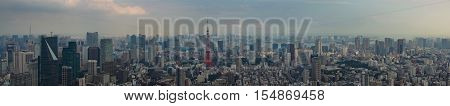 Tokyo Japan - September 26 2016: Panorama of Tokyo skyline shot off Observatory tower. Red Tokyo tower stands out in center of photo. Multitude of buildings under cloudy late afternoon sky.
