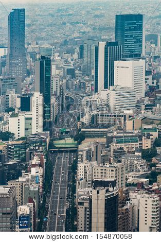 Tokyo Japan - September 26 2016: Aerial view since shot off Observatory tower. A broad highway cuts through downtown Tokyo between highrises and other buildings. An ocean of concrete.