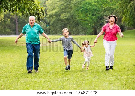 Happy Multigeneration Family Of Grandparents And Grandchildren Running In The Park poster