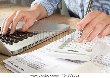 Hands Using Calculator And Laptop For Accounts