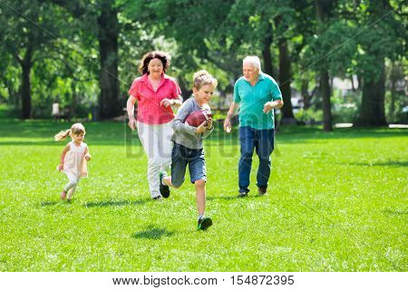 Happy Grandparents Playing With Rugby Ball And Having Fun The Park