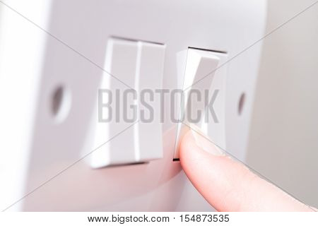 Finger Turning On Light On A 4 Gang Switch Plate