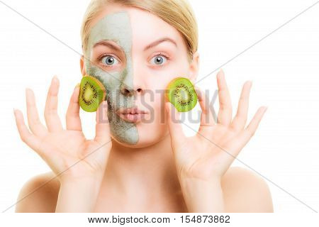 Skin care. Surprised woman in clay mud mask on face holding slices of kiwi fruit isolated. Girl taking care of dry complexion.