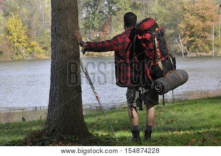 Back view of traveler with backpacking and trekking equipment looking at the water