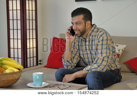 Hispanic young man talking on cell phone while relaxing at home