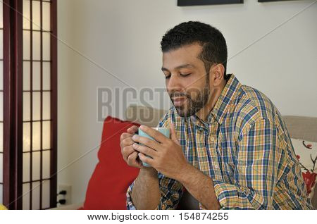Bearded Hispanic man enjoying a warm cup of morning coffee or tea