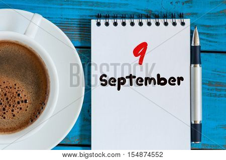 September 9th. Day 9 of month, coffee or tea cup with loose-leaf calendar on designer workplace background. Autumn time. Empty space for text.