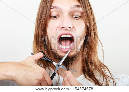 Fear of shaving cutting beard. Young scared terrified man boy with scissors cut his hair on chin. Bearded man shave face.