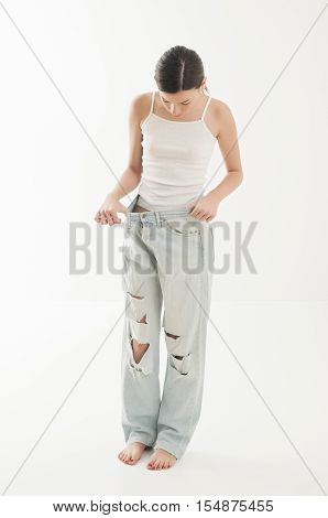Young girl holding huge pants to show of weight loss