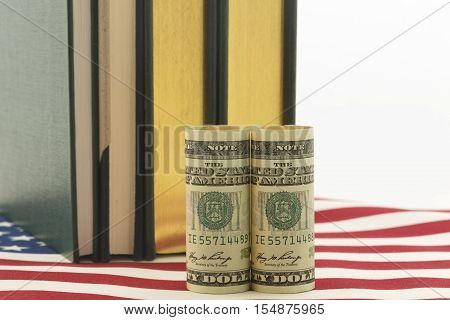 American currency in front of books on stars and stripes pattern. Symbols reflect issues of cost investment needs and governmental policy related to education.