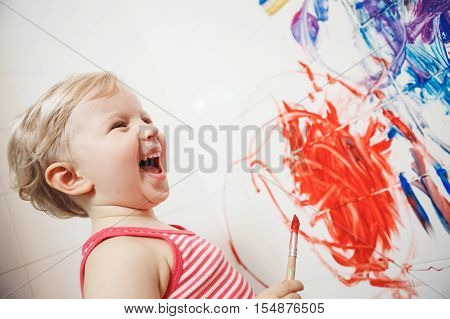 Portrait of cute adorable white Caucasian little boy girl playing and painting with paints on wall in bathroom having fun lifestyle childhood concept