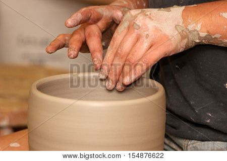 A potter's hands as she works on the wheel to create a bowl
