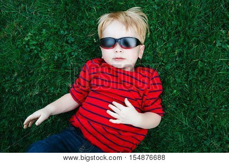 Close up portrait of funny cute adorable white Caucasian toddler child boy with blond hair in red pullover sunglasses lying on green grass. View from above top overhead.
