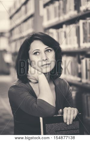 Black and white closeup portrait of thoughtful middle age mature woman student in library looking away teacher librarian profession back to school concept
