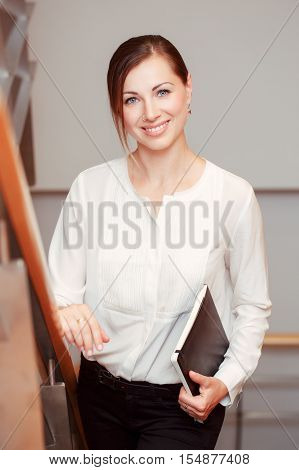 Portrait of beautiful smiling nice young white Caucasian business woman with blue eyes wearing white office blouse shirt and black pants looking in camera slavic Russian European face
