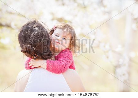 Close up portrait of caucasian mother in white dress holding hugging her daughter in pink clothes with funny face expression on sunny spring summer day in the park outside