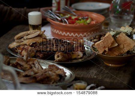 Traditional Macedonian food different kind of meat, salats, breads, beer and Rakia - krvavica sausage with shopska salad, shallow dof