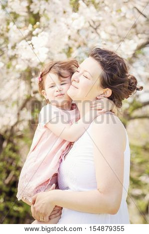Portrait of caucasian pregnant mother in long white dress holding and kissing her daughter in pink clothes on spring summer day in park outside among blooming cherry trees