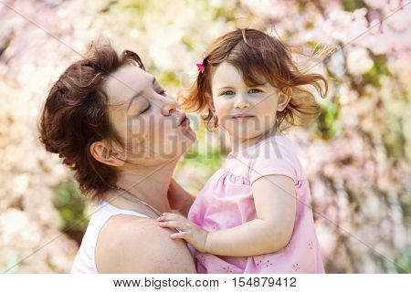 Closeup portraits of caucasian mother with daughter on a spring summer day in the park outside kissing