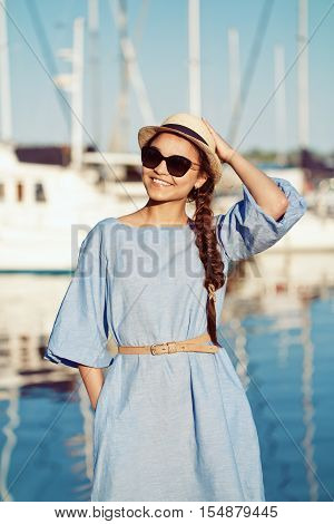 Portrait of smiling white Caucasian brunette woman with tanned skin in blue dress hat by seashore lakeshore with blurry yachts boats on background on water sunset on summer day lifestyle concept