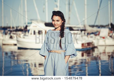 Portrait of beautiful white Caucasian brunette woman with tanned skin in blue dress by seashore lakeshore with blurry yachts boats on background on water sunset on summer day lifestyle concept