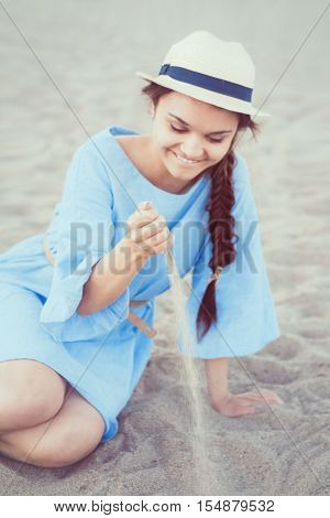 Portrait of smiling white Caucasian brunette woman with tanned skin in blue dress and straw hat sitting on sand beach shore sunset on summer day lifestyle concept