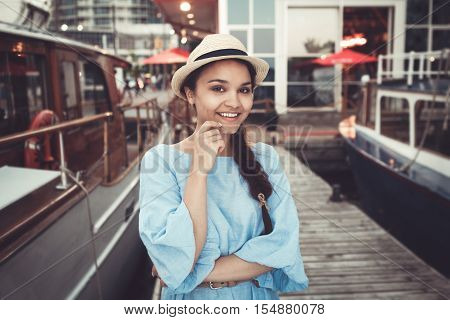 Portrait of beautiful smiling white Caucasian brunette girl on boat yacht pier quay in blue dress and straw hat navy maritime retro vintage style concept