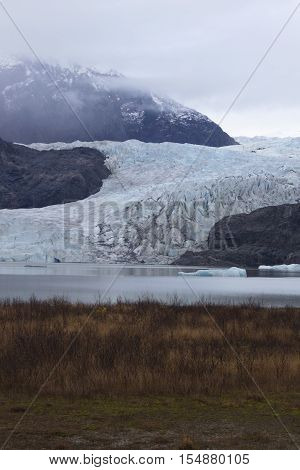 Vertical image displaying the visible retreat of Mendenhall Glacier in Juneau Alaska. Foreground formerly of land and dried grasses and glacier melt lake formerly was alpine glacier. Date is November 9 2015.
