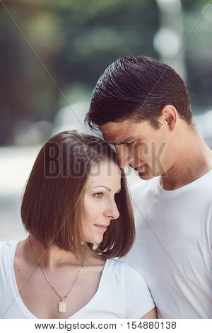 Closeup portrait of beautiful touching romantic couple man woman in love on spring summer day outside hugging kissing looking away from camera