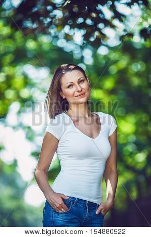 Portrait of beautiful innocent Caucasian adult girl woman with long hair bob style hazel eyes in white tshirt and blue jeans standing in park street outside looking away from camera