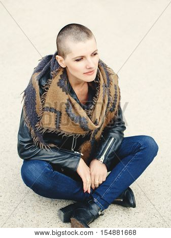 Portrait of beautiful Caucasian white young bald girl woman sitting on ground outside with shaved hair head in jacket scarf shawl jeans looking away toned with Instagram filters in yellow color