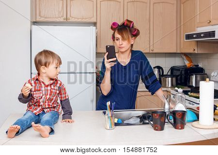Busy white Caucasian young woman mother housewife with hair-curlers in her hair taking pictures of things objects utensils in her kitchen her kid child son boy sitting beside her eating a cookie smiling and playing crazy busy life