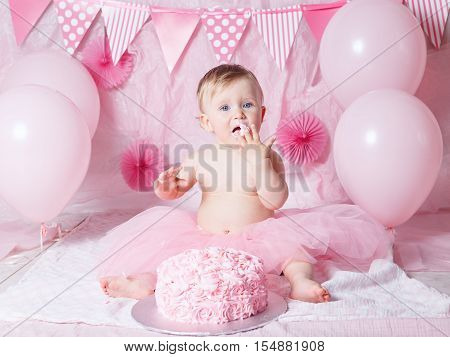 Portrait of cute adorable Caucasian baby girl with blue eyes in pink tutu skirt celebrating her first birthday with gourmet cake and balloons looking in camera cake smash first year concept