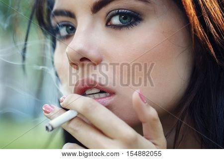 Closeup portrait of white Caucasian beautiful young sexy brunette woman with light blue green eyes smoking cigarette looking in camera toned with Instagram filters bad unhealthy habit