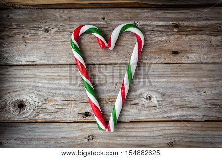 horizontal image of two large red and green candy canes formed in a heart shape in the middle of an old rustic wood background with lots of empty space for text.