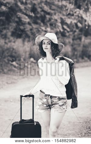 Black and white portrait of beautiful Caucasian young girl woman in white sweater shorts straw hat standing with travel bag on the wild country road in forest looking in camera wanderlust adventure vacation