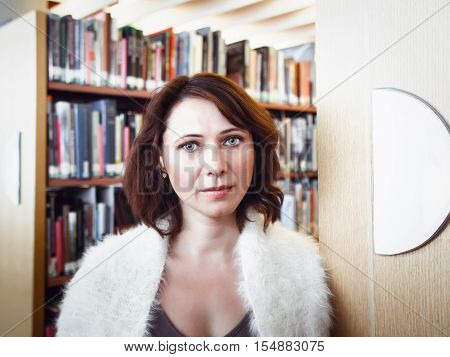 Closeup portrait of middle age mature brunette Caucasian woman student in library looking directly in camera teacher librarian profession back to school concept