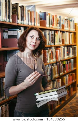 Portrait of middle age mature brunette Caucasian woman student with glasses in library holding book looking directly in camera teacher librarian profession back to school concept