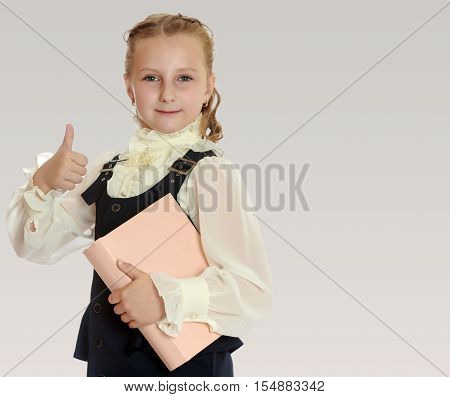 Dressy girl schoolgirl in black dress and white blouse holding a textbook and shows thumb. Gesture all right. Close-up.On a gray background.